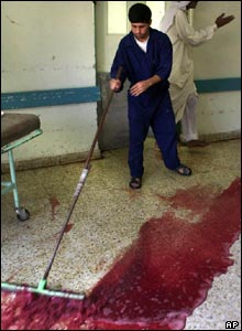 A hospital worker cleans blood from the halls of a hospital in Falluja, Iraq