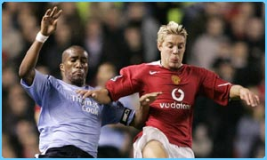 Manchester United's Alan Smith challenges Sylvain Distin of Manchester City