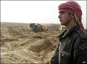 Bulldozer makes new ditch on border as Syrian soldier stands by