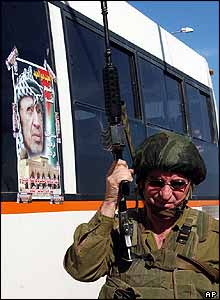 Israeli soldier by Palestinian bus in Nablus