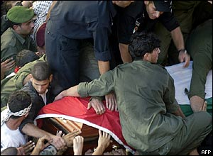 Palestinians clamber onto the coffin as it passes through the crowd