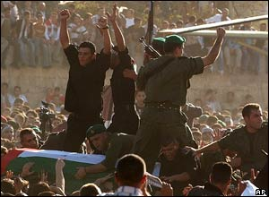 The coffin containing the remains of Palestinian leader Yasser Arafat is carried over the heads of the crowd