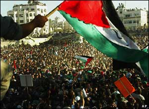 A Palestinian flag is waved above a crowd of people in Ramallah