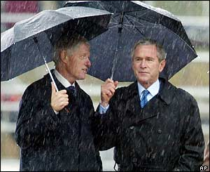 Bill Clinton and George W Bush chat under umbrellas in the pouring rain