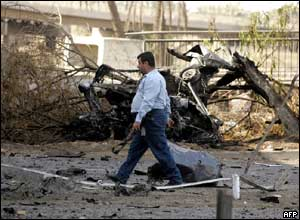 An Iraqi policeman walks past a truck which drove off a bridge in Baghdad