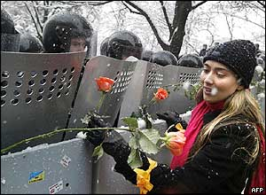 A woman placing flowers on the shields of riot police