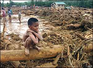 A young Filipino villager sits on debris of tree trunks, branches and mud littered on a road in Infanta, 30 November 2004