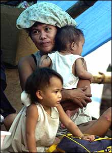 A woman clutches her siblings as they relocate to higher grounds in Pulilan town, Bulacan province, north of Manila on Thursday, Dec. 2, 2004.