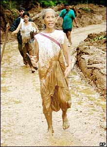 Olympia Romantico, 75, is covered in mud as she leads her family to an evacuation site after landslides buried hundreds in the township of Real, in Quezon province, 01 December 2004