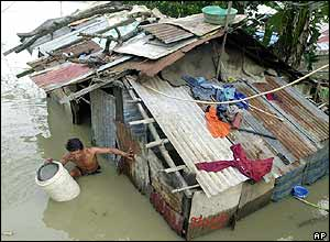 A man salvages a bucket from inside his submerged house near a riverbank in Pulilan town, Bulacan province, north of Manila on Thursday Dec. 2, 2004