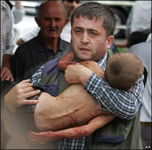 A man carries an injured child who escaped from a seized school in Beslan