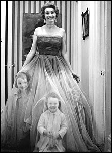 Patricia Neal wearing a ballgown, with three small children standing underneath the top, translucent layer of the skirt. All are laughing at the camera.
