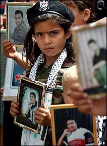 Palestinian girl in a police beret holds a portrait of a jailed relative