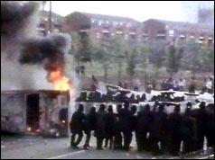 Police form a line next burning upturned car