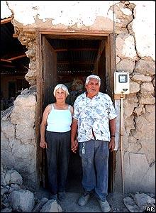 Ana Arancibia y su esposo Ramón Anaya frente a la entrada de su hogar destruido en Huara