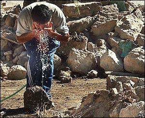 Un residente de Huara se lava el rostro entre los escombros de su hogar
