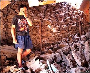 Un hombre entre las ruinas de su hogar en Huara