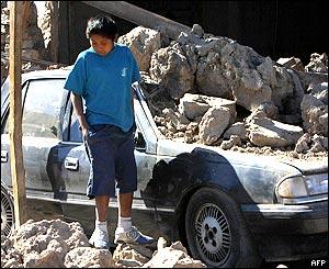 Una niña camina junto a un auto cubierto por rocas en Huara