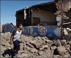 Un niño pasa delante de casas destruidas en Huara