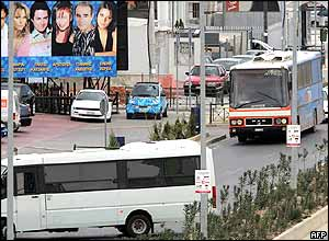 An elevated view of the bus and the white police bus blocking the road