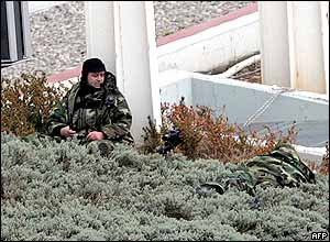 Special forces troops in camouflage gear hide in bushes