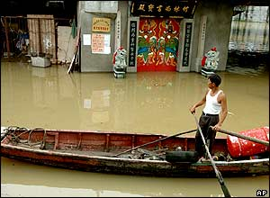 A man rows a boat in a flooded street in Fuzhou, Fujian province, eastern China