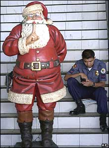 An anti-riot police officer sits besides a statue of Santa Claus as they are deployed in different streets leading to the presidential palace Wednesday, Dec. 22, 2004 in Manila.