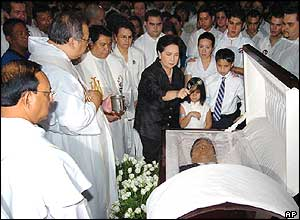 Widow Susan Roces surrounded by priests and relatives sprinkles holy water on the remains of her late husband during a mass at the Santo Domingo church in suburban Quezon City, 22 December 2004..