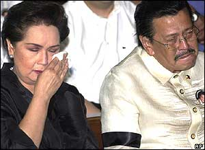 Ousted President Joseph Estrada, right, tries to control his tears as the widow and movie actress Susan Roces wipes her tears during a mass for FPJ, Dec. 22, 2004.