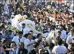 The horse-drawn hearse of former Philippine presidential candidate Fernando Poe Jr. passes by a Manila boulevard during his funeral Wednesday 22 Dec, 04