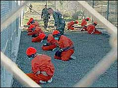 Prisoners kneeling in front of guards at Camp X-Ray