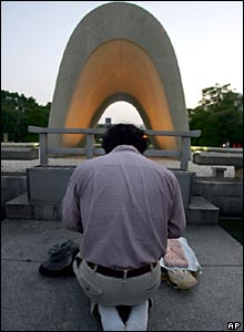 A man prays in front of the Hiroshima cenotaph