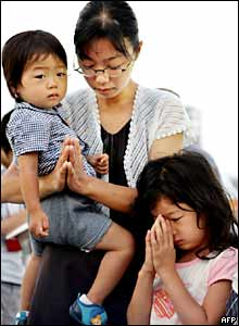 A mother and children pray at Hiroshima Peace Park