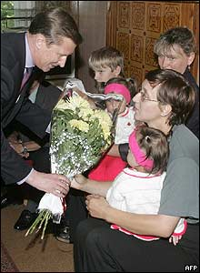 Defence Minister Sergei Ivanov (left) gives flowers to the submarine commander's wife