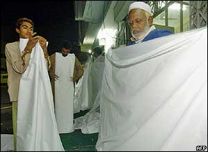 Members of a Pakistani non-governmental organisation, the Edhi Welfare Foundation, prepare burial shrouds for the victims of the 26 December tsunamis at their offices in Karachi