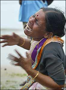 A woman cries near the body of her child, unseen, who was killed by tidal waves at Silver Beach in Cuddalore, India, on Monday