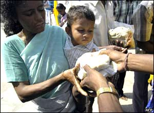 An Indian woman and her child receive bread from a relief volunteer