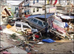 Three cars on top of one another along a street in Patong, Thailand