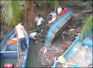 People working around overturned boats in Penang, Malaysia.