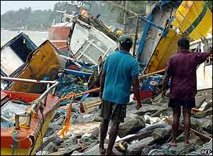 Sri Lankan residents stand in front of stranded fishing boats on a shore, 29 December 2004 in Paiyagala, south of the capital Colombo