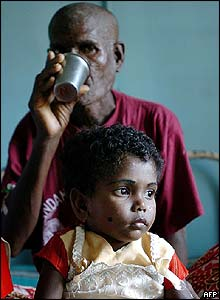 Refugee at hospital in Port Blair drinks water with his granddaughter