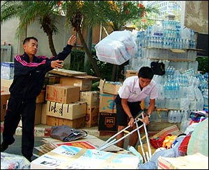 Workers in Bangkok, Thailand, load boxes of aid into trucks