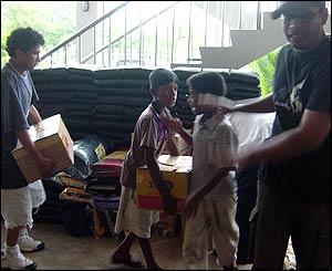 Young children in Sri Lanka load boxes in their home for victims of tsunami
