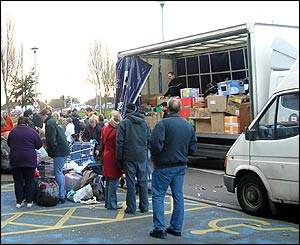 Residents of Cardiff, Wales collect aid and load it onto vehicles for disaster victims