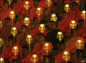 Buddhist monks hold candles during a memorial service in Thailand