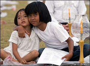 Two young Thai girls hug during a candlelit memorial service in Thailand