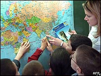 Teacher and pupils finding Thailand on a map