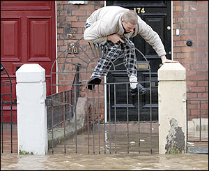 A resident climbs above flood water in Carlisle