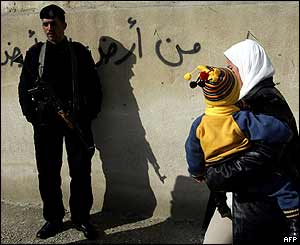 Palestinian woman with her baby on her way to vote walks by Palestinian policemen in the West Bank town of Abu Dis