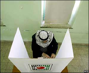 A Palestinian prepares his vote behind a polling booth in the village of Ain Ariq on the outskirts of Ramallah